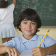 Boy writing in notebook while girl writes on blackboard in classroom — Stockfoto