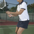 Senior Asian woman playing tennis - Stock Photo