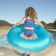 Young girl holding inner tube next to swimming pool - Stock Photo