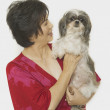 Studio shot of Asian woman with Shih-Tzu — Stock Photo