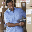Male African warehouse worker scanning packages — Stok fotoğraf