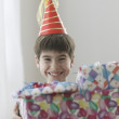 Young boy smiling with birthday presents - Stock Photo