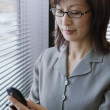 Businesswoman using her cell phone — Stockfoto