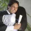 Stock Photo: Graduating mand womhugging each other