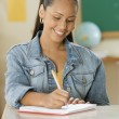 Stock Photo: Female Dominicteenager writing in her notebook in classroom