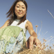 Middle-aged woman picking through long grass — Stock Photo