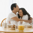 Hispanic couple hugging at the breakfast table — Stock Photo