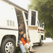 Couple sitting in doorway to recreational vehicle — Stock Photo