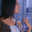 Hispanic woman looking through beaded curtain - Stock Photo