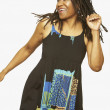 Studio shot of middle-aged African woman dancing - Stock Photo