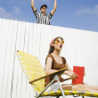 Hispanic referee making call over fence - ストック写真