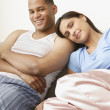 Couple wearing pajamas and smiling on sofa — Stockfoto
