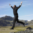 Businessman jumping off rocks in deserted rural area — Stock Photo