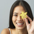 Asian woman holding star fruit over eye — Stock fotografie