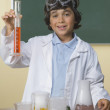 Young boy in science class holding beaker - Stock Photo