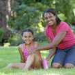 African mother putting sunscreen on daughter outdoors - Stock Photo
