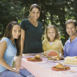 Portrait of Hispanic family at picnic table - Stock Photo
