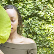Stock Photo: Womholding leaf in front of face outdoors