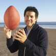 Portrait of man throwing football at beach - Foto de Stock