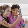 Two girls taking their own photograph with cell phone — Stock Photo #13224337