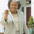 African female real estate agent holding keys to house — Stock Photo