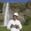 Man with hard hat and clipboard in front of waterfall — Stock Photo
