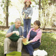 Hispanic grandparents and granddaughter gardening - Stock Photo