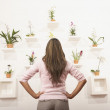 Businesswoman admiring wall of flowers — Stock Photo