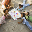 African mother coloring with daughters - Stock Photo