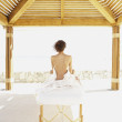 Woman sitting up on massage table outdoors -  