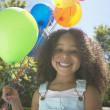 Close up of African girl holding balloons - Stock Photo
