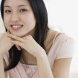 Asian woman with chin on hands — Stock Photo