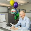 Senior businessman smiling in a cubicle with a bunch of retirement balloons — Stock Photo