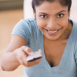 Indian woman changing channel with remote control — Stock Photo