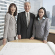 Senior Asian businessman and businesswomen looking at blueprints — Stock Photo