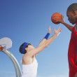 African man holding basketball away from nerd — Stock Photo