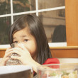 Young Asian girl drinking water at the table  — Stock Photo