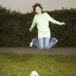 Young woman jumping for joy while dog watches - Stockfoto