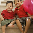 Foto Stock: Portrait of Asian brothers holding balloon