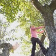 Low angle view of Hispanic girl climbing tree — Stock Photo