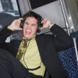 Businessman listening to headphones on a train — Stock Photo