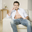 Man sitting on sofa with shirt unbuttoned — Stock Photo