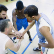 High angle view of coach and basketball players in huddle — Stock Photo