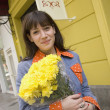 Hispanic woman with flowers on sidewalk - Stockfoto
