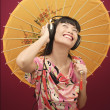 Woman with headphone and umbrella — Stock Photo