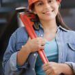 Hispanic female construction worker holding a wrench — Stock Photo