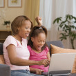 Mother and daughter using a laptop together — Stok fotoğraf