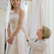Young bride being fitted in her dress - Stock Photo