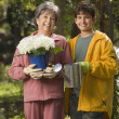 Grandmother and grandson with potted plant and watering can — Stockfoto