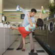 Stock Photo: Couple dancing with soap in laundromat